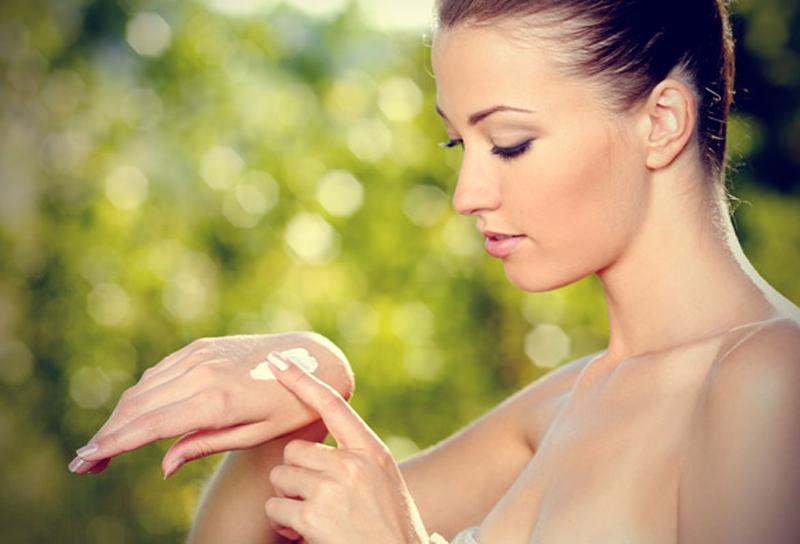 Женщина мажет руки кремом