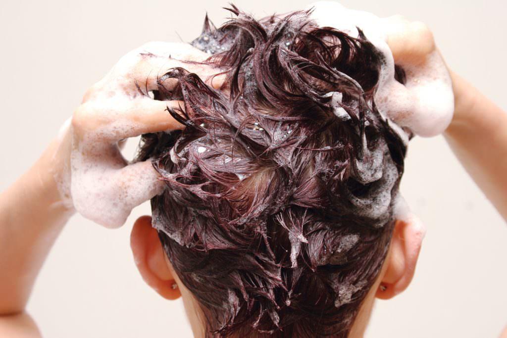 Мужчина моет голову шампунью от грибка