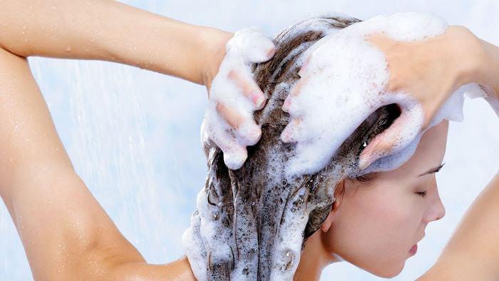 Девушка намыливает волосы