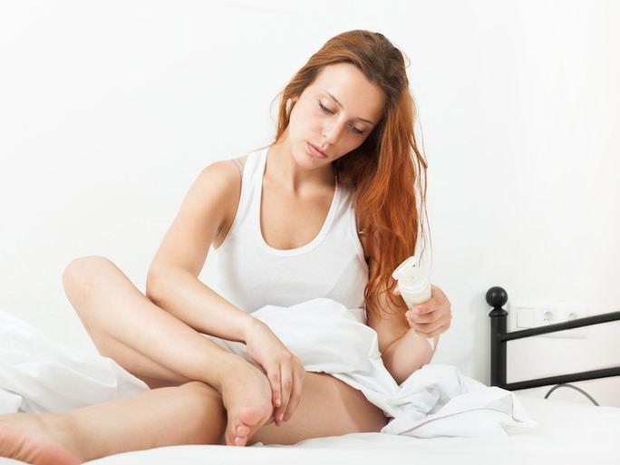 Женщина мажет ноги